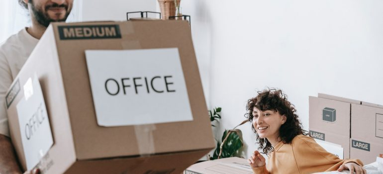 man carrying moving box labeled office