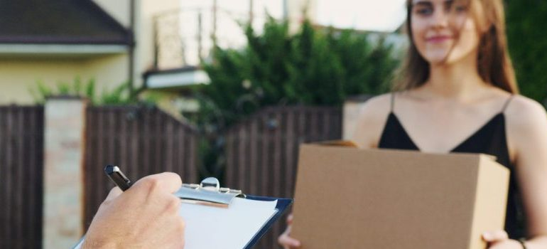 person creating a moving checklist, female holing a cardboard box