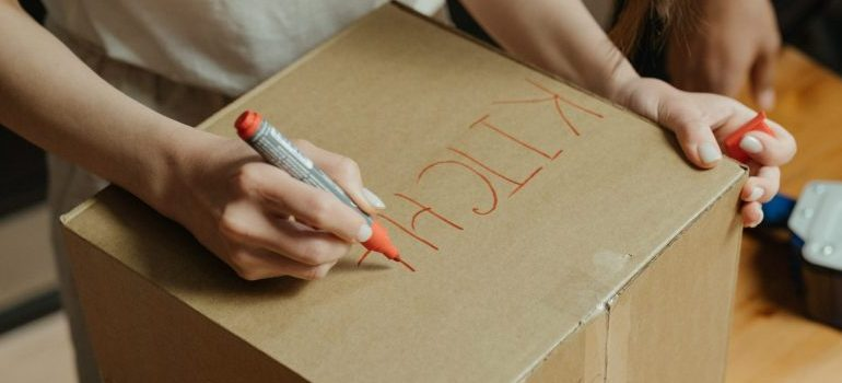 person labeling a cardboard moving box