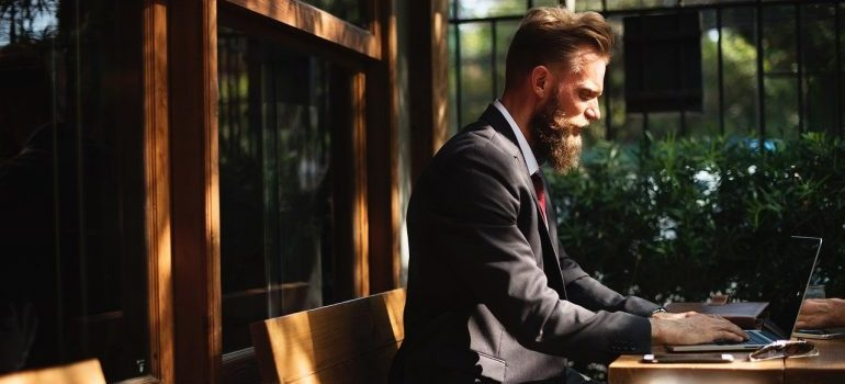 A man in a suit working on a laptop.