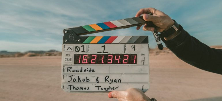 Women's hands hold a clapperboard, to mark the beginning of filming, with sand, far hills and sky on the background
