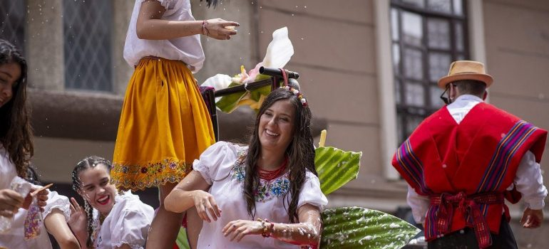 Females laughing during festivity in the North Hills, seating and standing surrounded with baskets woven of reeds and big leaves sprayed with white crème and old man with a red poncho and a straw hat walking away
