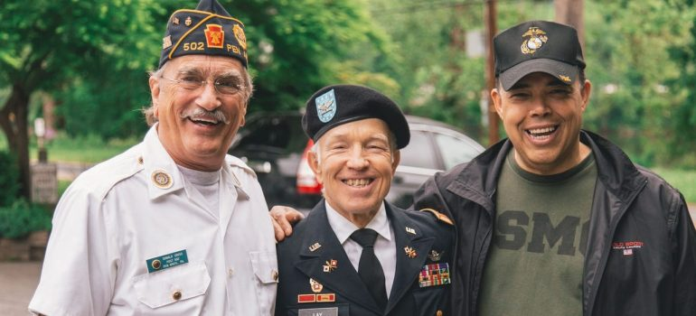 Three veterans in uniforms and with decorations hugging and smiling while picture, and you have to be ready for such scenes when prepare for moving to North Hills
