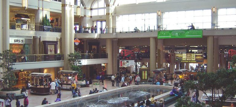 People walking and seating around the big fountain on the ground floor, with shops in the background of the big shopping mall, that you can see if you move to Burbank this year