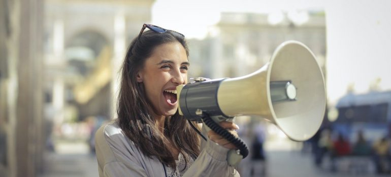 Woman with long hair and grey sweater, with sunglasses on top of her head is using megaphone.