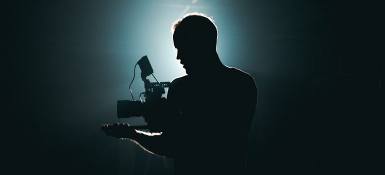 a man in the dark holding a filming camera