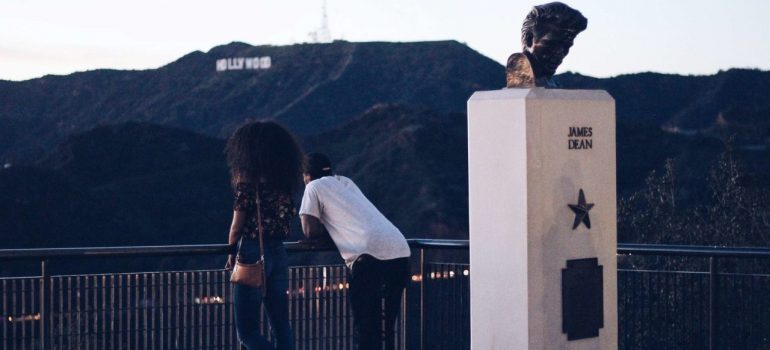 two people looking at the Hollywood sign as one of top places in San Fernando Valley for future actors